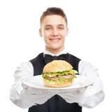 Młody szczęśliwy uśmiechnięty kelnera mienia hamburger na talerzu zdjęcia stock