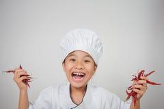 Młody szefa kuchni chwyta chili w oba rękach Obrazy Stock