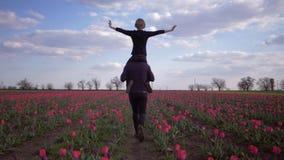 Młody tata z dziecko chłopiec rozszerzania się rękami popierać kogoś obsiadanie na ramię bieg wokoło przez kwiat łąkę tulipany zbiory