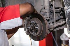Młody technik załatwia hamulcowego dyska w samochodowym garażu obrazy royalty free