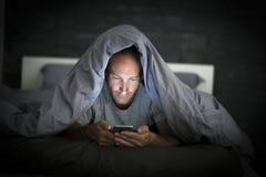 Młody telefonu komórkowego nałogowa mężczyzna obudzony przy nocą w łóżkowym używa smartphone póżno obraz royalty free