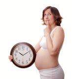 Młody toughtfull kobieta w ciąży z zegarem Zdjęcie Stock