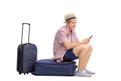 Młody turysta pisać na maszynie wiadomość na telefonie komórkowym Fotografia Stock