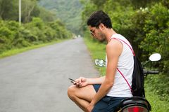 M?ody turysta siedzi na do wynaj?cia motocyklu sprawdza smartphone z okularami przeciws?onecznymi obraz stock