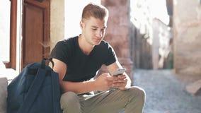 Młody turysta z plecaka obsiadaniem przy wejściowymi schodkami i używać telefonem komórkowym zbiory wideo