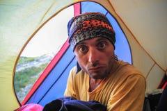 Młody turystyczny facet siedzi wśrodku żółtego namiotu przy campsite fotografia royalty free