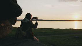 Młody turystyczny kobiety backpacker fotografuje krajobraz na jej smartphone kamerze po wycieczkować na skale przy zmierzchem Zdjęcia Royalty Free