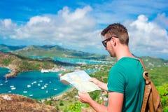 Młody turystyczny mężczyzna z mapy tłem angielszczyzny Ukrywa od Shirley wzrostów, Antigua, raj zatoka przy tropikalną wyspą Fotografia Stock