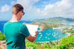 Młody turystyczny mężczyzna z mapy tłem angielszczyzny Ukrywa od Shirley wzrostów, Antigua, raj zatoka przy tropikalną wyspą Zdjęcia Stock