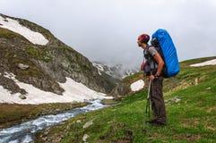 Młody turystyczny odpoczywać na wierzchołku przegapia dolinę zdjęcie stock