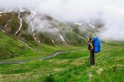 Młody turystyczny odpoczywać na wierzchołku przegapia dolinę fotografia stock