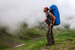 Młody turystyczny odpoczywać na wierzchołku przegapia dolinę fotografia royalty free