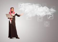 Młody uśmiechnięty arab z laptopem pokazuje wirtualne ikony chmura ilustracja wektor