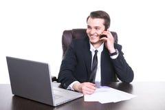 Młody uśmiechnięty biznesmen pracuje przy biurem na laptopie na telefonie komórkowym i ono uśmiecha się, opowiadający fotografia stock