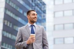 Młody uśmiechnięty biznesmen z papierową filiżanką outdoors Zdjęcia Royalty Free