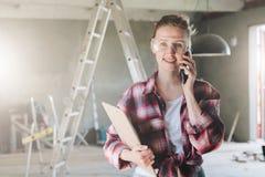 Młody uśmiechnięty bizneswomanu budowniczy, inżynier, architekt, projektant opowiada na komórce w budów szkłach stoi, Zdjęcia Royalty Free
