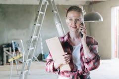 Młody uśmiechnięty bizneswomanu budowniczy, inżynier, architekt, projektant w budów szkłach stoi Obrazy Stock