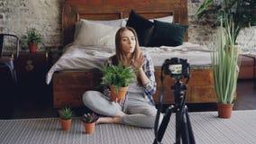 Młody uśmiechnięty blogger w przypadkowej odzieży trzyma kwiaty, opowiada wideo blog dla onlinego vlog wokoło i nagrywa, zbiory