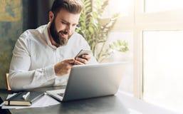 Młody uśmiechnięty brodaty biznesmena obsiadanie przy stołem przed komputerem, używać smartphone Mężczyzna sprawdza emaila, gawęd Zdjęcia Royalty Free