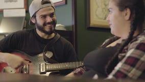 Młody uśmiechnięty brodaty mężczyzna bawić się gitarę w barze, atrakcyjna tłuściuchna kobieta siedzi blisko śpiewu Czas wolny prz zbiory