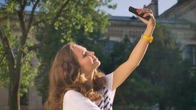 Młody uśmiechnięty caucasian brunetki obsiadanie w parku na trawie, używać smartphone, robi selfie, uniwersytet w zbiory