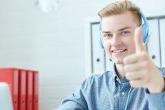 Młody uśmiechnięty caucasian centrum telefoniczne konsultant z słuchawki up w biurowym pokazuje kciuku zdjęcie stock
