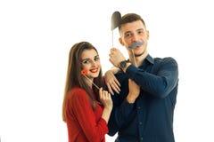 Młody uśmiechnięty facet z dziewczyną, trzyma blisko twarz papieru wsparć w postaci warg, wąsa i kapeluszy dla fotografii, Fotografia Stock