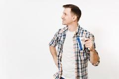 Młody uśmiechnięty gospodyni mężczyzna w w kratkę koszulowy patrzeć na boku, trzymający szczotkarski dla czyścić odizolowywam na  obrazy stock