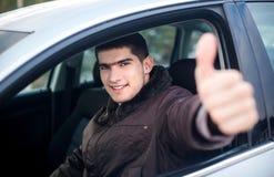 Młody uśmiechnięty kierowcy kciuk up w samochodzie Obraz Royalty Free