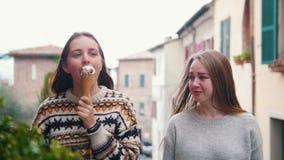 Młody uśmiechnięty kobiety łasowania lody, inny kobiety spęczenie i płacz i zbiory