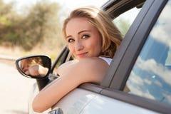 Młody uśmiechnięty kobiety obsiadanie w samochodowym bierze kluczu Obraz Stock