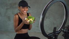 Młody uśmiechnięty kobiety vlogger opowiadać, pokazuje aprobaty podczas gdy nagrywający jej dziennego sprawności fizycznej diety  zbiory