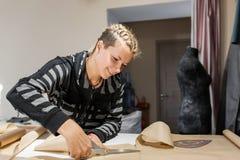 Młody uśmiechnięty krawiecki nożycowy matrycuje dla robić odziewa fotografia stock