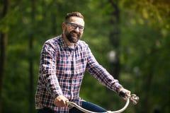 Młody uśmiechnięty mężczyzna jazdy rower przy parkiem Fotografia Stock