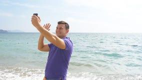 Młody uśmiechnięty mężczyzna ma wideo wzywał mądrze telefon przy denną plażą Szczęśliwy facet robi wideo online gadkom na pięknym Fotografia Royalty Free