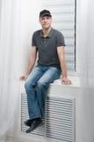 Młody uśmiechnięty mężczyzna obsiadanie na białym okno Fotografia Stock