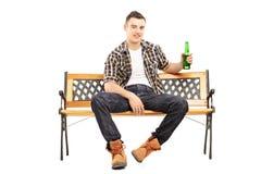 Młody uśmiechnięty mężczyzna obsiadanie na mieniu i ławce piwna butelka Fotografia Royalty Free
