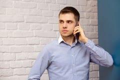 Młody uśmiechnięty mężczyzna opowiada telefon komórkowego patrzeje Odosobnioną białą ściana z cegieł błękita koszula obraz stock