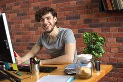 Młody uśmiechnięty mężczyzna pracuje przy jego miejsce pracy obraz stock
