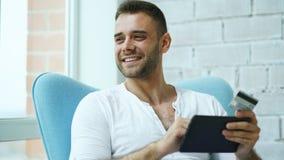 Młody uśmiechnięty mężczyzna robi online zakupy używać cyfrowej pastylki komputerowego obsiadanie przy balkonem w domu Zdjęcie Royalty Free