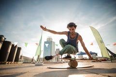 Młody uśmiechnięty mężczyzna utrzymuje balansowym na tle miasta buil obrazy stock
