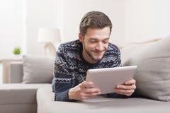 Młody uśmiechnięty mężczyzna z pastylka komputerem w ręce w domu Zdjęcia Stock