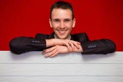 Młody uśmiechnięty mężczyzna z pustą czerwień znaka deską Zdjęcie Stock