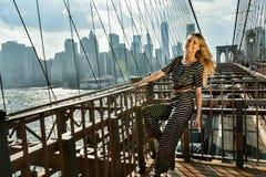 Młody uśmiechnięty model pozuje przy mostem w gorącym letnim dniu jest ubranym modnego kombinezon Fotografia Royalty Free