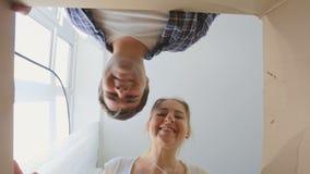 Młody uśmiechnięty pary otwarcia karton i patrzeć inside zdjęcie wideo