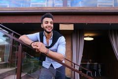 Młody uśmiechnięty przystojny męski Arabski pojawienie opiera na piersi brzęczeniach Zdjęcie Royalty Free