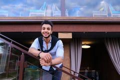 Młody uśmiechnięty przystojny męski Arabski pojawienie opiera na piersi brzęczeniach Zdjęcia Stock