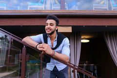 Młody uśmiechnięty przystojny męski Arabski pojawienie opiera na piersi brzęczeniach Obrazy Stock