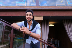 Młody uśmiechnięty przystojny męski Arabski pojawienie opiera na piersi brzęczeniach Zdjęcia Royalty Free
