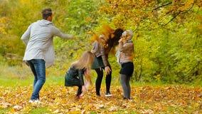 Młody uśmiechnięty rodzinny miotanie opuszcza wokoło na jesień dniu outdoors zbiory